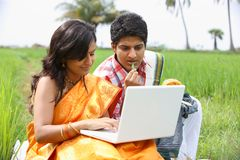 Couple sitting in the paddy field. Asian couple sitting in the paddy field with their laptop Royalty Free Stock Photo