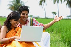 Couple sitting in the paddy field. Asian couple sitting in the paddy field with their laptop Royalty Free Stock Image