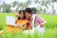 Couple sitting in the paddy field. Asian couple sitting in the paddy field with their laptop Royalty Free Stock Images