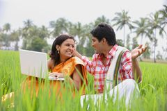 Couple sitting in the paddy field. An asian couple sitting in the paddy field with their laptop Stock Images