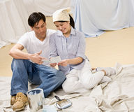 Couple sitting with paint can and color swatch. Preparing to decorate home interior royalty free stock photo