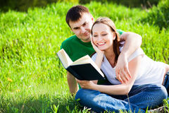 Couple sitting in park reading book. Couple sitting in summer park reading book Royalty Free Stock Image