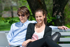 Couple sitting in park and using laptop Stock Photo