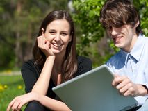 Couple sitting in park and using laptop Stock Images