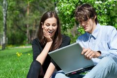 Couple sitting in park and using laptop Royalty Free Stock Photography