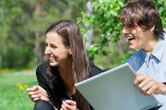 Couple sitting in park and using laptop Royalty Free Stock Photos
