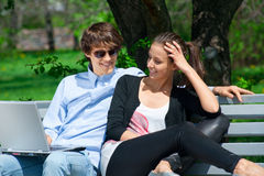Couple sitting in park and using laptop Stock Image