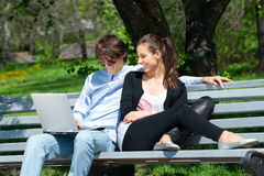 Couple sitting in park and using laptop Royalty Free Stock Photo