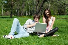 Couple sitting in park and using laptop Royalty Free Stock Image