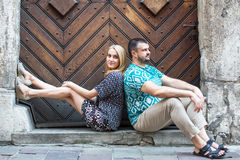 Couple sitting on the pavement with backs to each other. Love. Royalty Free Stock Images