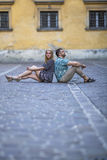 Couple sitting on the pavement with backs to each other. Royalty Free Stock Image