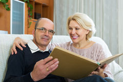 Couple sitting with photograph album Royalty Free Stock Photography