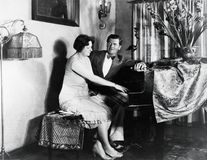 Couple sitting at piano royalty free stock image