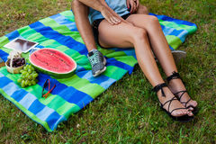 Couple sitting on a picnic blanket and eating fruits Stock Photos