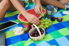 Couple sitting on a picnic blanket and eating fruits Royalty Free Stock Photos