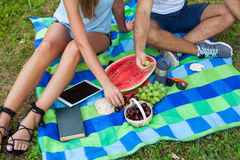 Couple sitting on a picnic blanket and eating fruits Stock Images