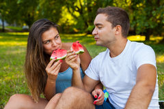 Couple sitting on a picnic blanket and eating watermelon. Royalty Free Stock Photos