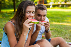 Couple sitting on a picnic blanket and eating watermelon. Stock Photo