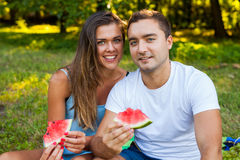 Couple sitting on a picnic blanket and eating watermelon. Stock Photography