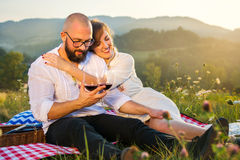 Couple sitting on a picnic blanket with wine glasses Royalty Free Stock Images