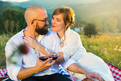 Couple sitting on a picnic blanket with wine glasses Stock Images