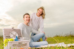Couple sitting on a picnic under the white sky Stock Photos