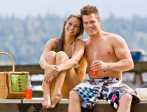 Couple sitting on pier Stock Images