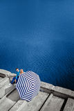 Couple sitting on the pier with beach umbrella on the water on b Stock Photography