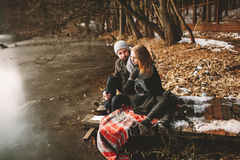 Couple sitting on pier at frozen lake looking at each other stock images