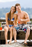 Couple sitting on pier with soda Royalty Free Stock Photos