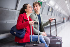 Couple sitting at platform. Happy young couple sitting at underground platform awaiting train Stock Photos