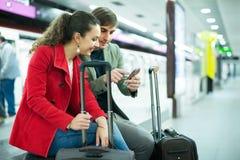 Couple sitting at platform. Young couple sitting at underground platform awaiting train Royalty Free Stock Images