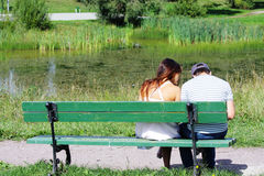 Couple sitting at pond Stock Photography