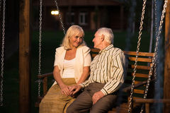 Couple sitting on porch swing. Royalty Free Stock Photos