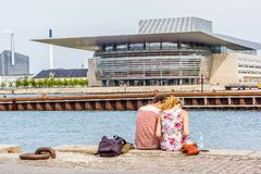 Couple sitting on the  quayside in front of the Copenhagen Opera Stock Photography
