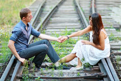 Couple sitting on railway Stock Image