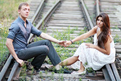 Couple sitting on railway Stock Images