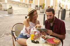 Couple sitting and reading guidebook in coffee shop, Ibiza, Spain Stock Image