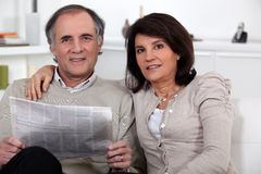 Couple sitting reading a newspaper Royalty Free Stock Photo