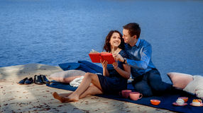 Couple sitting and reading on terrace near the water Stock Image