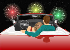 Couple sitting in red convertible car enjoying a fireworks show Royalty Free Stock Photography