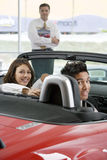 Couple sitting in red convertible in car showroom, salesman in background, smiling, portrait Royalty Free Stock Photo
