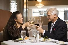 Couple sitting at restaurant. Caucasian mature adult male and prime adult female sitting at restaurant table toasting wine glasses Royalty Free Stock Photos