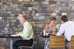 Couple sitting at restaurant table, smiling, mature businessman working on laptop at next table Royalty Free Stock Photo