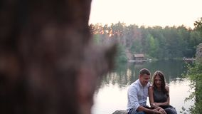 Couple sitting on the river bank in forest stock video footage