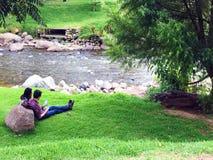 Couple sitting on River Bank of Rio Tomebamba in Cuenca, Ecuador stock photography