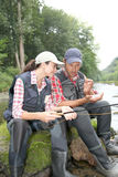 Couple sitting in river with fishing lines Stock Photos