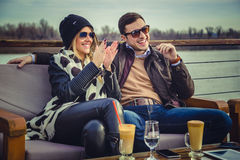 Couple sitting by the river and laughing Royalty Free Stock Photos