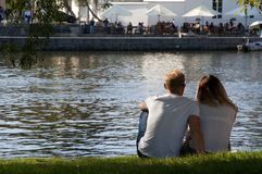Couple sitting on a riverbank. PRAGUE, CZECH REPUBLIC- SEPTEMBER 12, 2015: couple sitting on a riverbank stock image