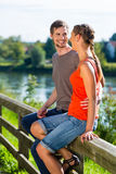 Couple sitting at riverbank in summer Stock Images